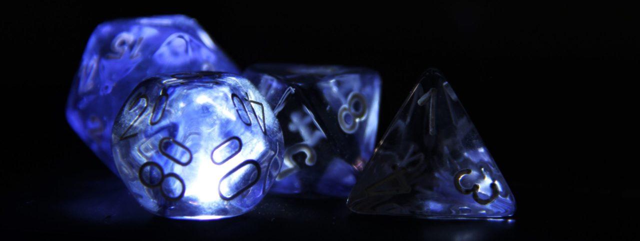 Leuchtende Rollenspiel-Würfel vor schwarzem Hintergrund